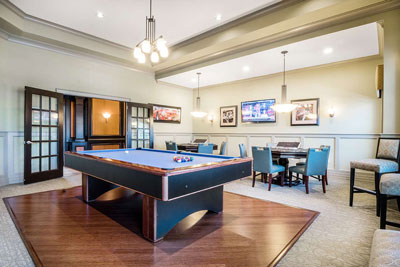 Resident entertainment area with billiard table, smaller card tables, and artwork on the walls