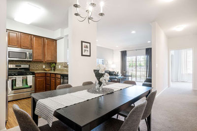 View of apartment dining room and kitchen furnished with kitchen appliances and dining room table